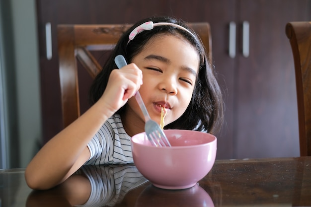 Asian little kid enjoying eating noodle