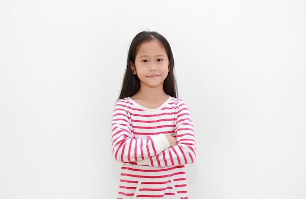 Азиатская маленькая девочка скрестила руки с улыбкой на белом фоне