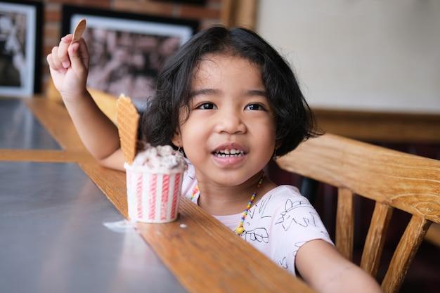 Азиатская маленькая девочка показывает счастливое лицо, едя чашку мороженого