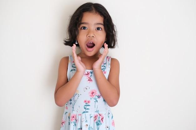 Азиатский маленький ребенок девочка показывает выражение лица «вау», изолированные на белом фоне