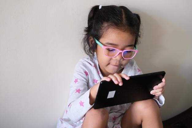 모바일 태블릿 장치를 사용하여 노는 동안 방사선 방지 안경을 쓴 아시아 어린 소녀