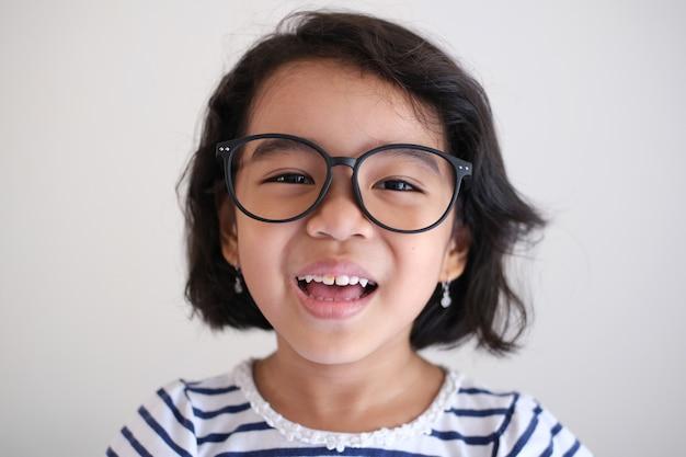 Азиатская маленькая девочка в очках и счастливая улыбка