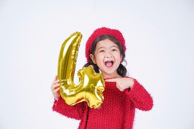 白い背景で隔離のホイル番号バルーンとアジアの小さな子供幸せな笑顔