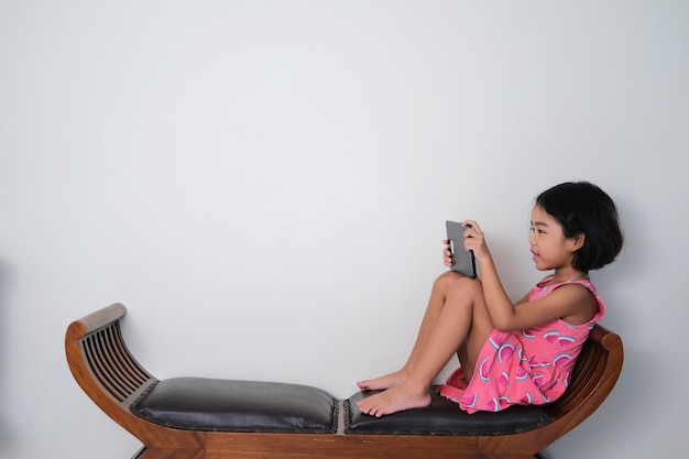Asian little kid seating in a wooden couch while playing game using her mobile tablet
