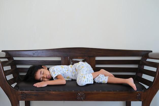 나무 소파에서 혼자 자고 있는 아시아 어린 아이