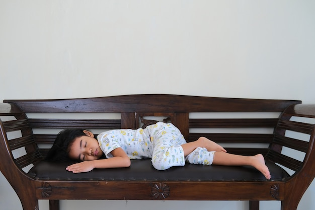 Asian little kid sleeping alone in wooden couch