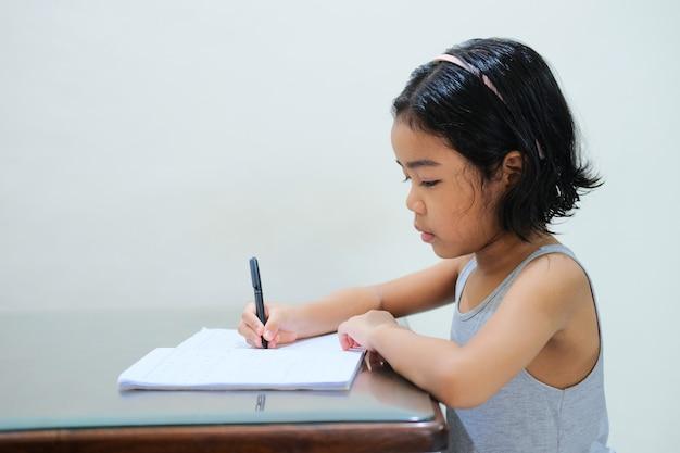 심각한 표정으로 테이블에서 공부하는 아시아 어린 아이