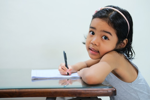 Asian little kid studying in the table and showing happy face expression