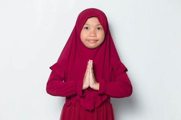 Азиатская маленькая мусульманская девушка в хиджабе показывает приветственный жест