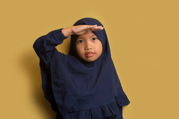Asian little muslim girl wearing hijab with hand over head.