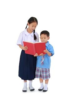 Азиатские маленькие школьник и девочка в тайской школьной форме стоя с книгой чтения изолированной над белой предпосылкой. полная длина с обтравочным контуром