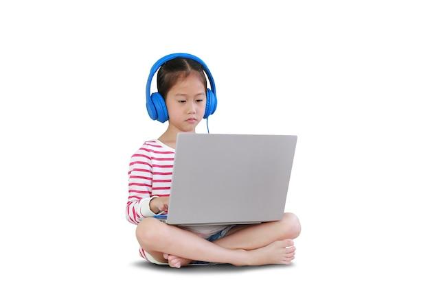 座ってヘッドフォンを使用してアジアの小さな女子高生は、白い背景で隔離のラップトップコンピューターによるオンライン学習クラスを勉強します。クリッピングパスのある画像