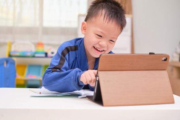 집에서 자신의 온라인 수업 중 숙제를 공부하는 노트북 컴퓨터를 사용하는 아시아 작은 남학생 아이