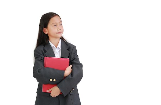 공식적인 셔츠를 입은 아시아 여학생, 흰색 배경에 격리된 채 책을 껴안고 있는 비즈니스 정장. 복사 공간 및 클리핑 패스가 있는 이미지