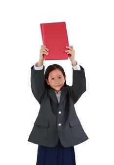 공식적인 셔츠를 입은 아시아 여학생, 흰색 배경에 격리된 카메라를 보면서 머리 위로 교과서를 들고 있는 학생복. 클리핑 패스가 있는 이미지