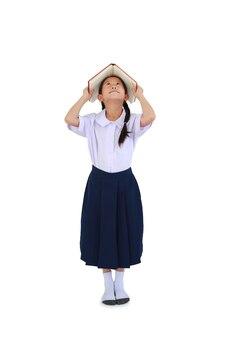 책 표지를 머리 위로 들고 흰색을 올려다보고 교복을 입은 아시아 여학생