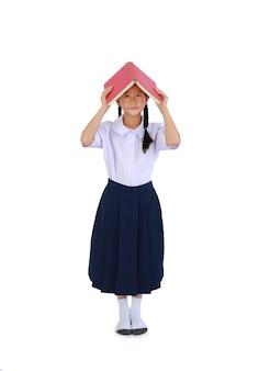 태국 교복을 입은 아시아 여학생이 흰색 배경에 격리된 머리 위로 책 표지를 들고 서 있습니다. 클리핑 패스가 있는 전체 길이