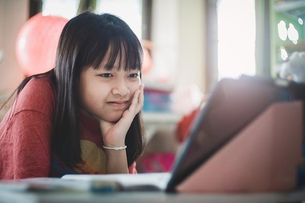 격리 기간 동안 미소와 행복, 사회적 거리, 온라인 교육 개념으로 집에서 온라인 수업을 하는 아시아 여학생