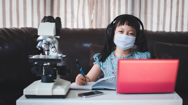 Азиатская маленькая школьница учится во время своего онлайн-урока дома с улыбкой и счастливой, социальная дистанция во время карантина, концепция онлайн-образования