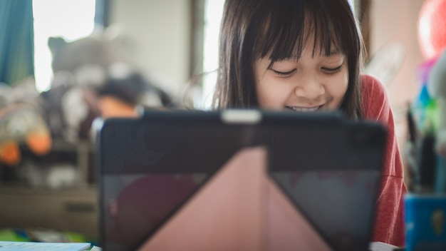 Asian little schoolgirl studying during her online lesson at home with smile and happy, social distance during quarantine,online education concept