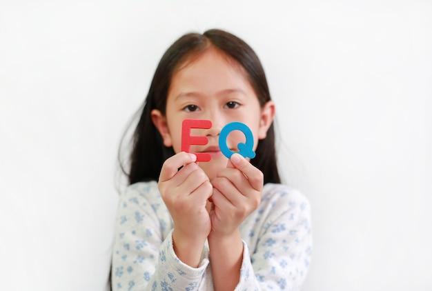 흰색 배경 위에 eq(감정 지수) 스폰지 텍스트를 들고 있는 아시아 어린 소녀입니다. 아이와 교육 개발 개념입니다. 그의 손에 있는 eq 텍스트에 초점
