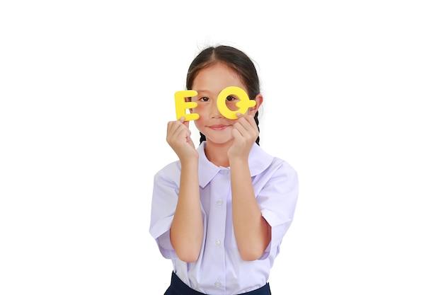 그녀의 얼굴과 눈에 알파벳 eq (감정 지수) 텍스트를 들고 학교 유니폼 아시아 어린 소녀 아이. 교육 개념. 클리핑 패스가있는 이미지