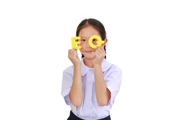 Asian little young girl child in school uniform holding alphabet eq (emotional quotient) text on her face and eyes. education concept. image with clipping path