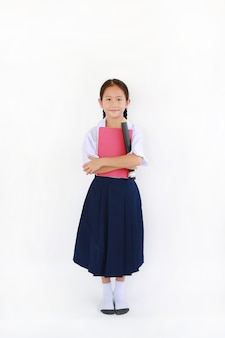 Asian little young girl child in thai school uniform standing with hugging a book and big pencil isolated on white background. full length