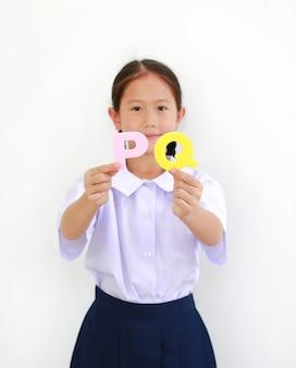 Азиатская маленькая молодая школьница в школьной форме показывает текст алфавита pq (положительный интеллект) на белом фоне. концепция образования