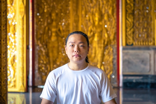 Asian long hair man relaxes meditation with all white costume sit in front of buddist's gold wallpaper in the temple, thailand.