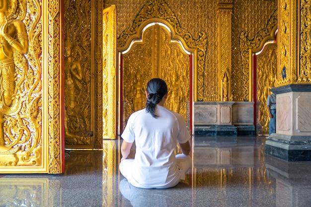 아시아의 긴 머리 남자는 태국 사원에 있는 buddist의 금색 벽지 앞에 흰색 의상을 입고 앉아 명상을 이완합니다.