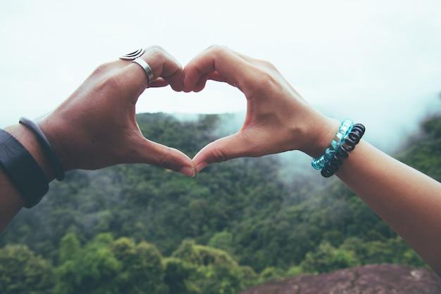 アジアの恋人カップルの女性と男性は自然を旅行します。手はハート型。自然と
