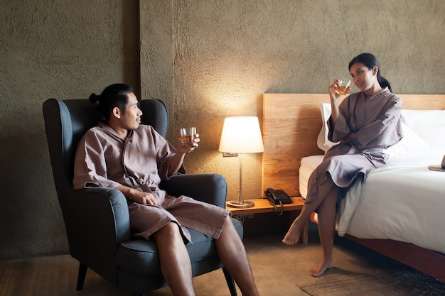 Asian lover drinking whisky together in bedroom. lifestyle or love concept