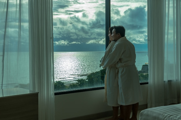 Asian lovers in bathrobe suit hugging and sightseeing the sea beach when waking up