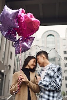 Asian lovers cuddling under umbrella rainy day.