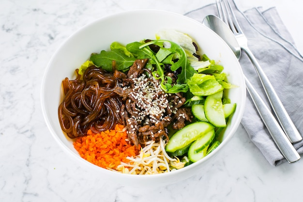 Asian lunch bowl with beef. noodles, mix green leaves and vegetables on marble table. close-up