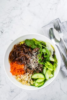 Asian lunch bowl with beef. noodles, mix green leaves and vegetables on marble table. top view, copy space
