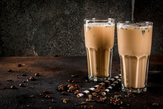 Asian malaysian traditional drink yuenyeung from tea coffee milk with ice cubes on dark rusty background