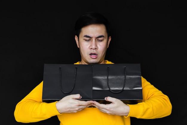 ブラックフライデーのコンセプトのために、アジア人男性が驚愕し、暗い背景に買い物袋を持っています。