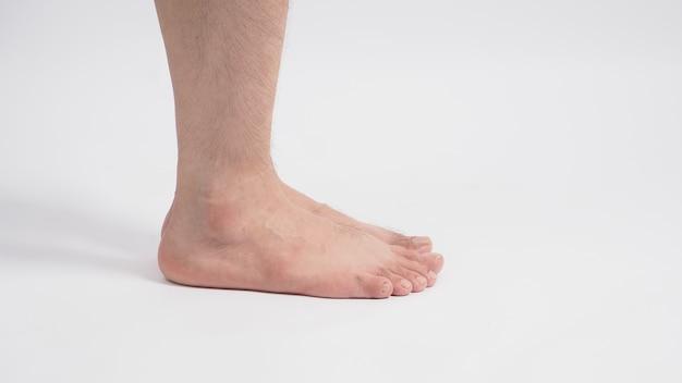 アジア人男性の裸足は白い背景で隔離されます。スタジオ撮影写真。