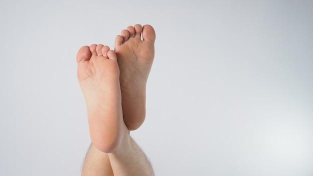 アジア人男性の裸足は白い背景で隔離されます。