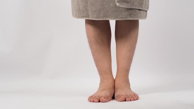 맨발로 아시아 남성이 서 있고 다리는 흰색 배경에 격리된 회색 목욕 수건으로 싸여 있습니다.