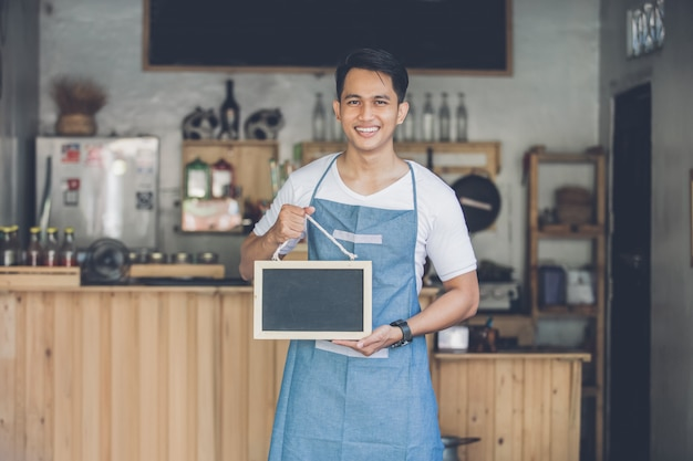 Asian male cafe owner with blank board