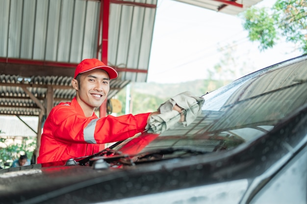 Asian male car cleaner wearing red uniform smiles while wiping car glass in car salon