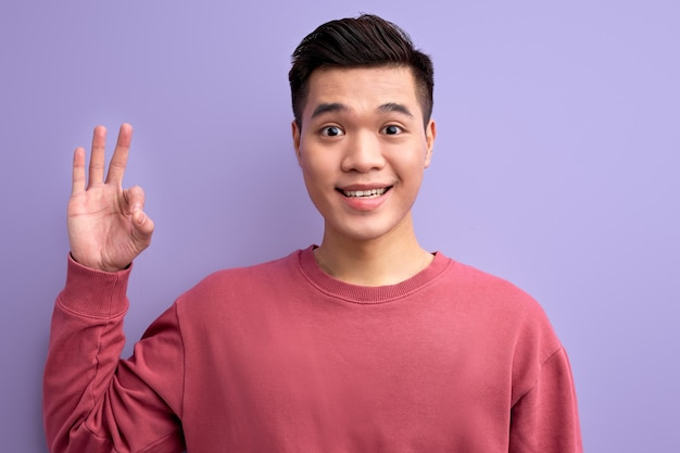 Asian male in casual wear showing ok gesture at camera, smiling