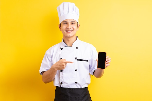 The asian male chef was pointing his finger at the cell phone he was holding