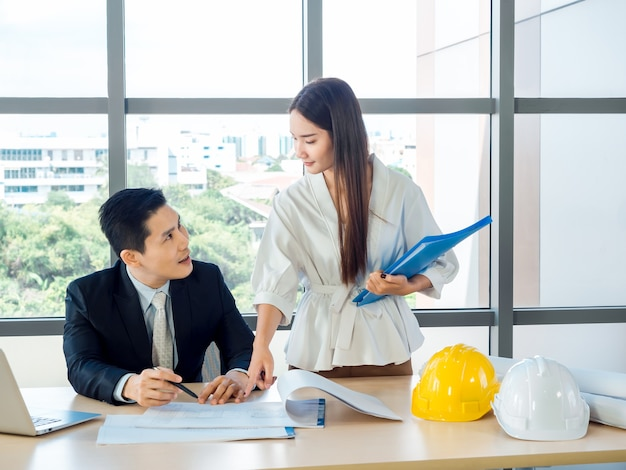 Asian male chief architect or engineer in suit and young female secretary discuss on blueprint with laptop computer and white and yellow hard hats on desk on huge glass window in office.