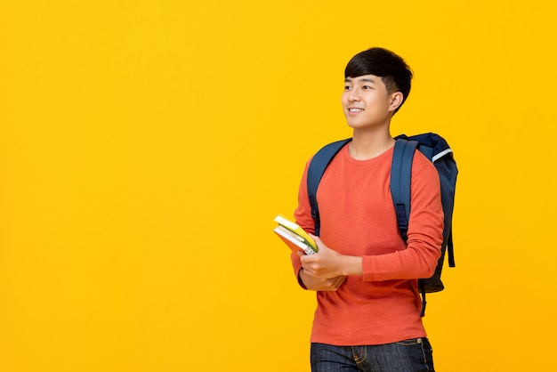 Asian male college student with backpack holding books