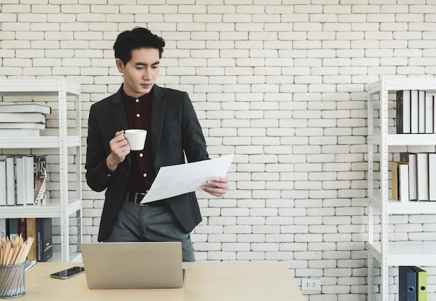 Asian male company manager standing at a desk in office, holding coffee cup, reading meeting information,  documents or resume form new employees waiting for job interviews.