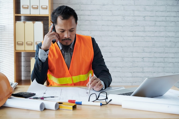 Asian male construction firm executive sitting in office and talking on phone